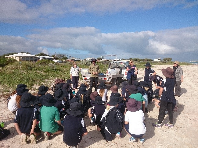 NACC Coastal and Marine Project Officer speaks to Lancelin Primary School students about coastal bush food used by traditional owners before tree planting.