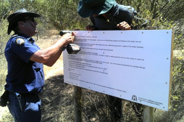 A prison guard helps erect signage Willi Gully Aboriginal Heritage Site